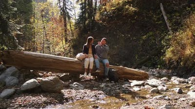 Man with His Girlfriend are Resting in Forest at Fall Day