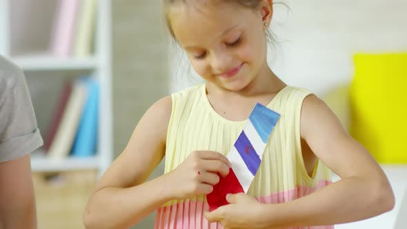 Cover Image for Happy Little Boy and Girl Smiling and Trying on Paper Neck Tie