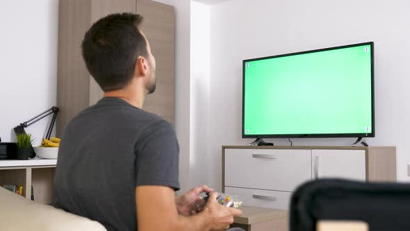 Thumbnail for Adult Man in Front of Big Green Mock-up Screen TV Playing a Video Game on the Console