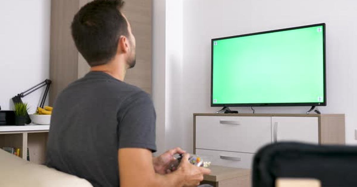 Adult Man in Front of Big Green Mock-up Screen TV Playing a Video Game on the Console