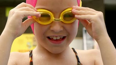 Cheerful Child Puts on Swimming Goggles for Swimming in the Pool