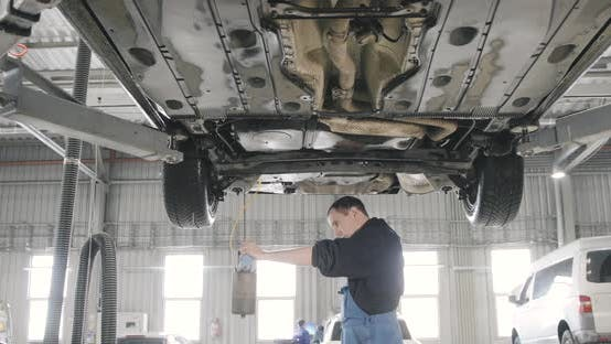 Car Auto Service Worker Cleans Tools
