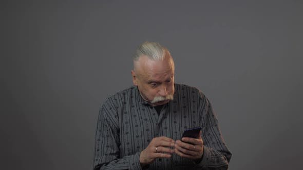 Thumbnail for Aged Man Holds Gadget Looks at Telephone Upsets and Cries