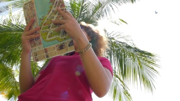 Thumbnail for Happy Travel Girl Look At Map Against Palm Tree
