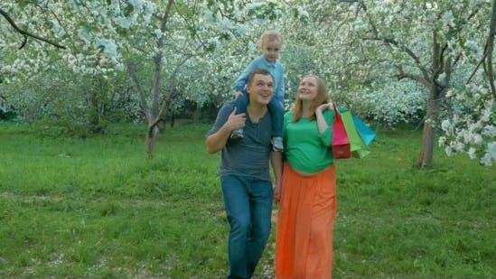 Thumbnail for Glückliche Familie mit Kind zu Fuß in Bloomy Park