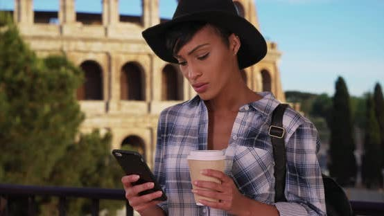 Thumbnail for African-American female in Rome uses phone while drinking coffee near Colosseum
