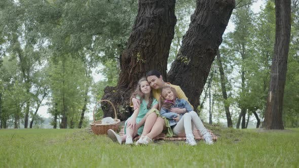 Thumbnail for Portrait Senior Cute Woman Kissing and Hugging Adorable Granddaughters Sitting on the Grass