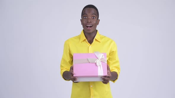Thumbnail for Young Happy African Businessman Opening Gift Box and Looking Surprised
