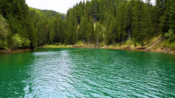 Aerial View on the lake between mountain forest. Over crystal clear mountain lake water. Fresh water