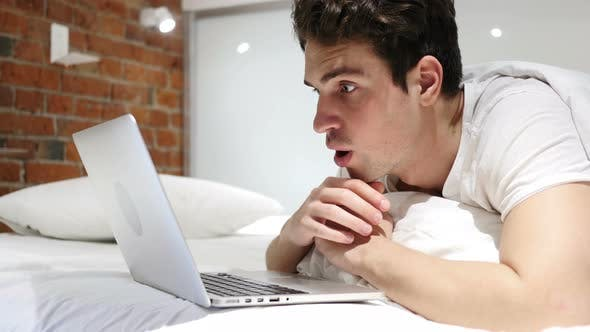 Man in Bed in Shock by Results on Laptop, Wondering