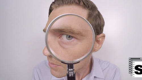 Businessman Looking Though Magnifying Glass