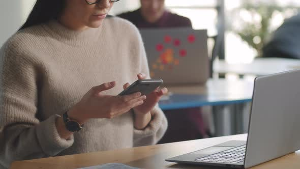 Woman Browsing the Web on Smartphone in Office