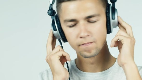 Cover Image for Man Listening To Music With Headphones On a White