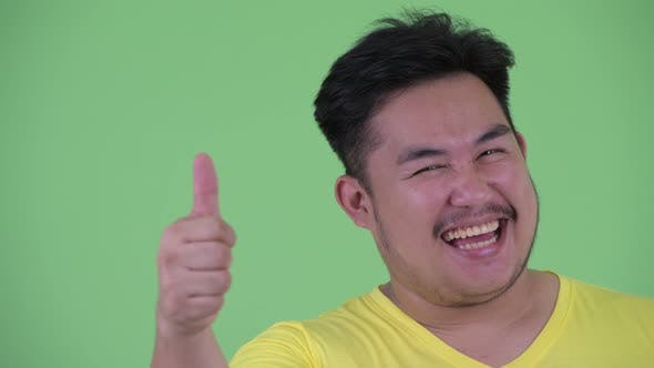 Thumbnail for Face of Happy Young Overweight Asian Man Giving Thumbs Up