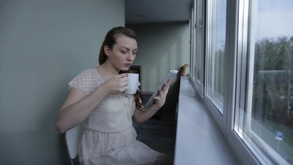 Thumbnail for Girl With Tablet Sitting By The Window And Drink