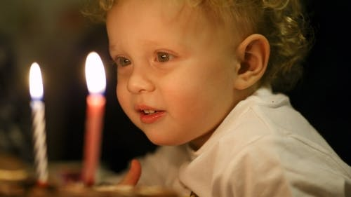 Little Boy Blowing Out Two Candles On His Birthday