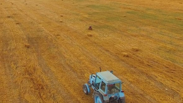 Thumbnail for Rural Tractor Making Hay Bales In Stubble Field