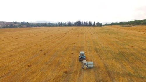 Tractor Baler Making Straw Bales In Stubble Field