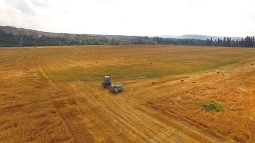 Tractor Baler Driving In Stubble Field