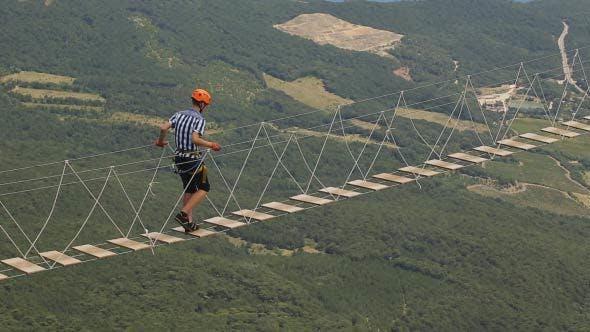 Thumbnail for Man Walking A Dangerous Suspension Bridge