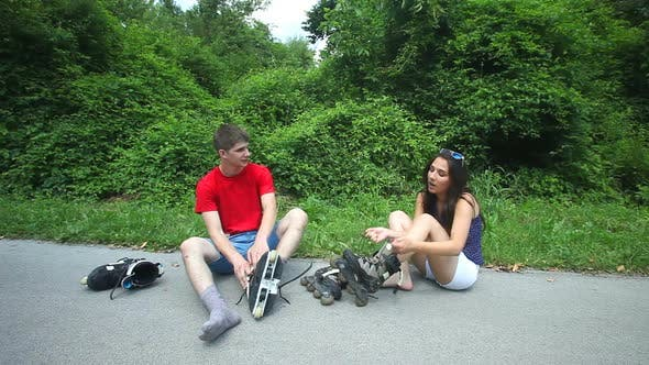 Thumbnail for Young Woman And Man Sitting On Track, Putting Their Rollerblades On Their Feet. 1