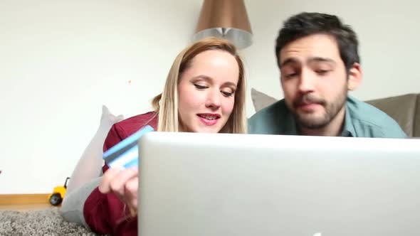 Thumbnail for Woman And Man Lying On Carpet In Living Room And Buying Online 1