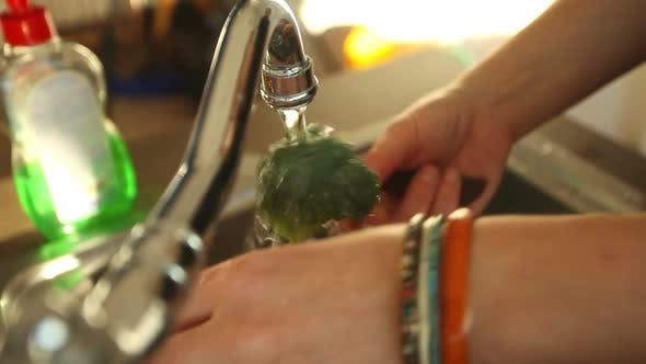 Thumbnail for Woman Cleaning Broccoli In Water Under Tap In Sink