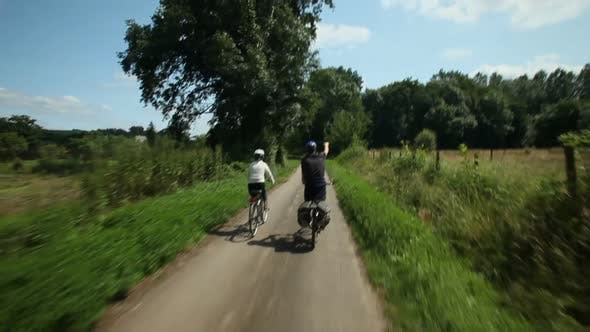 Thumbnail for Slow Motion - Retired Couple Cycling On Road In Village In France 1
