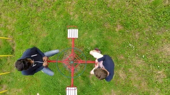 Thumbnail for Aerial View Of Two Men Spinning On Carousel In Park. 1