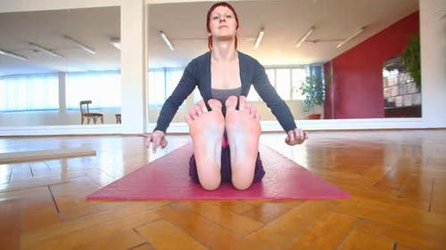Women Stretching Over Her Feet In Yoga Asana