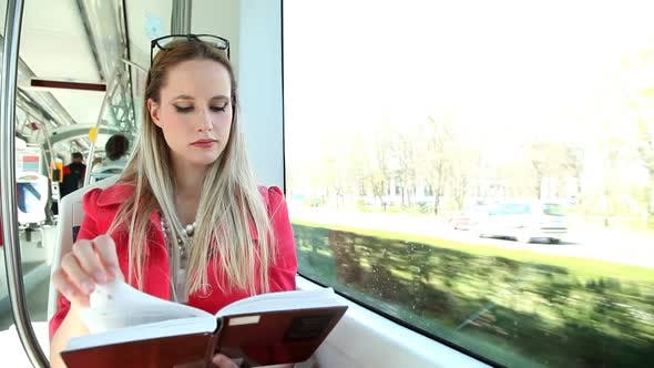 Thumbnail for Young Blond Woman Riding Tram, Reading Book On Sunny Day