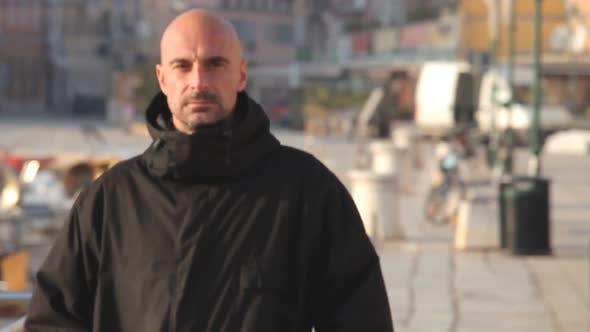 Thumbnail for Man In Black Jacket Walking Along Harbour