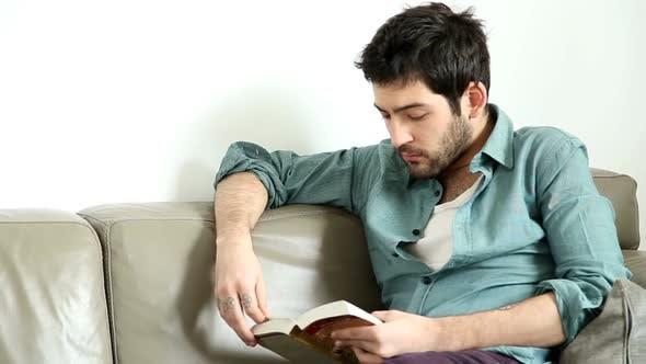 Thumbnail for Man Sitting In Living Room Reading Interesting Novel