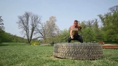 Muscular Man Hitting Tire With A Hammer With Only One Hand 2