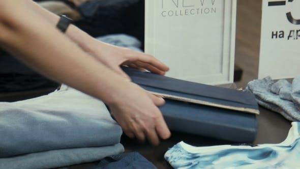 The Girl At The Counter Selects a Handbag
