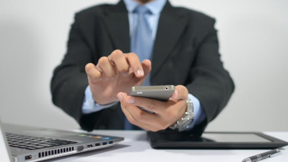 Thumbnail for Businessman Holding and Using Smartphone