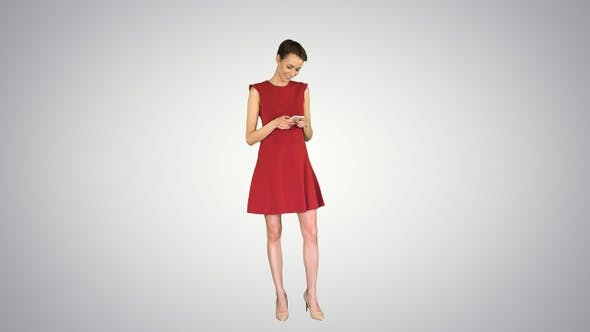 Thumbnail for Young Happy Attractive Female in Red Dress Texting on The
