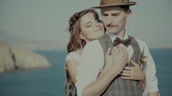 Bride Embraces Bridegroom's Chest Against The Sea