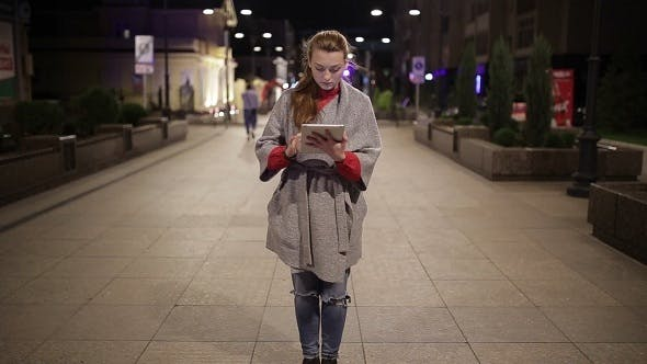 Thumbnail for A Young Girl Stands On The Boulevard With a Tablet