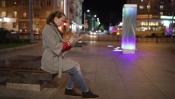 Thumbnail for Cute Woman Using Tablet Outdoors In The Evening.