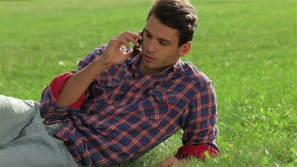 Thumbnail for Man Lying On The Grass Using Mobile