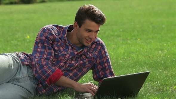 Cover Image for Man Lying On Grass At Park With Laptop