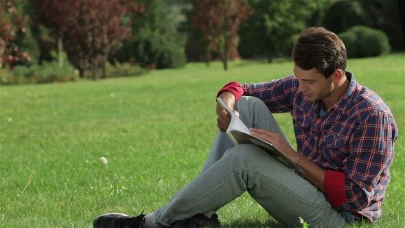 Thumbnail for Man Reading While Sitting On The Grass