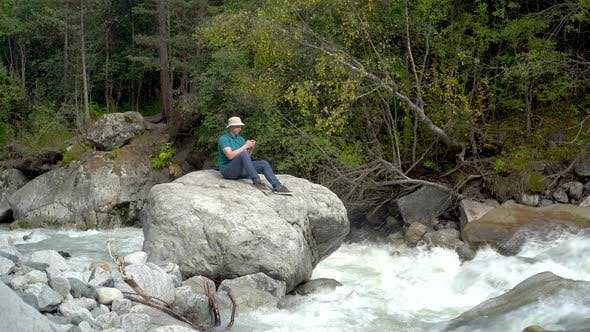 Thumbnail for A Young Man in a Panama Hat Sits on a Stone with a Phone in His Hands in the Mountains By the River.