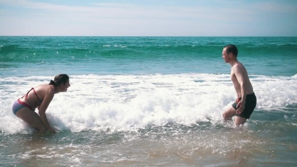 Thumbnail for Happy Couple Having Fun On Ocean Waves