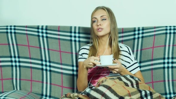 Cover Image for Attractive Woman On The Couch Listening To Music