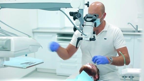 Thumbnail for Dentist Using a Dental Microscope