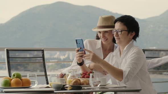 Women Take Selfie at Cafe Terrace Table