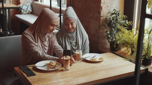 Thumbnail for Female Friends in Hijab Using Smartphone and Talking on Lunch in Cafe