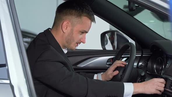 Thumbnail for Businessman Sitting in a New Car, Checking Out Interior of a Vehicle